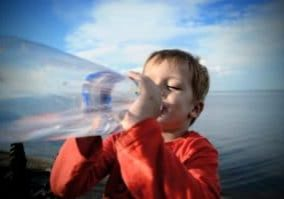 little-boy-drinks-from-a-water-bottle-while-walk-by-the-sea_t20_pY0OZY